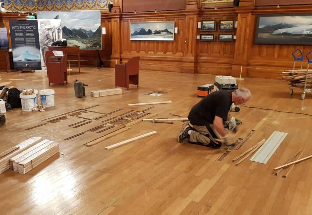Parquettiste en train de réparer les planches d'un sol en bois
