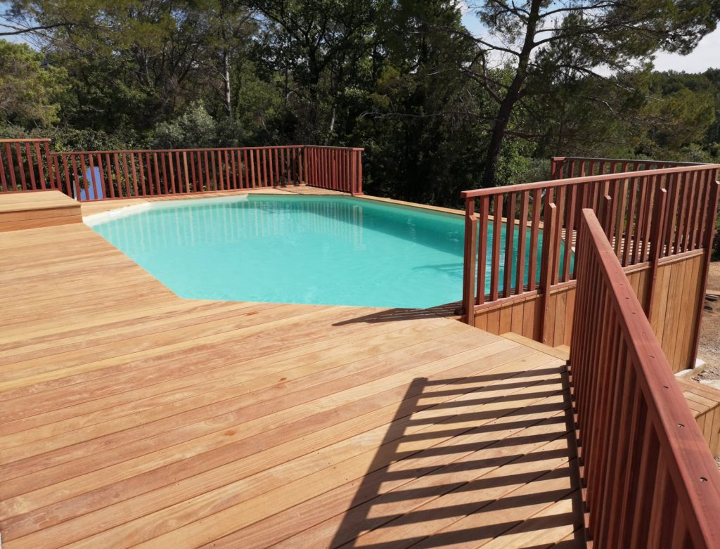 Une piscine avec une terrasse en hauteur et garde-corps en bois rouge.