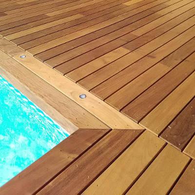 Une terrasse en bois avec un cadre autour de la piscine