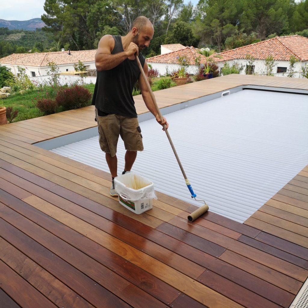 Menuisier en train d'appliquer un saturateur sur le bois d'une terrasse en ipé.