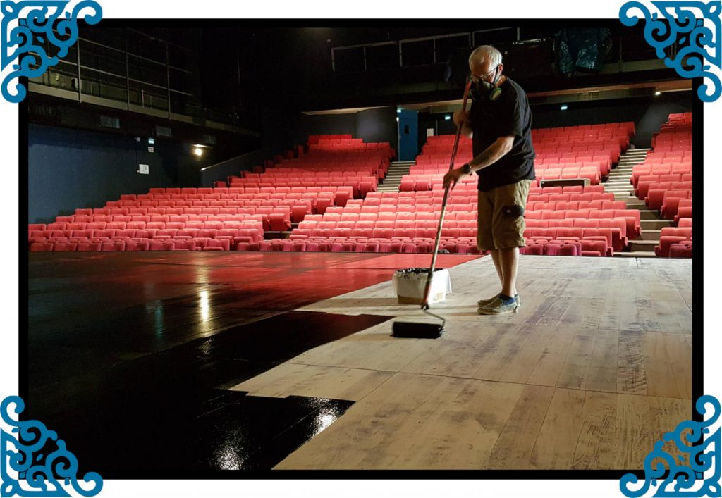 Artisan du parquet en train de couvrir une scène de théâtre avec une peinture noire.